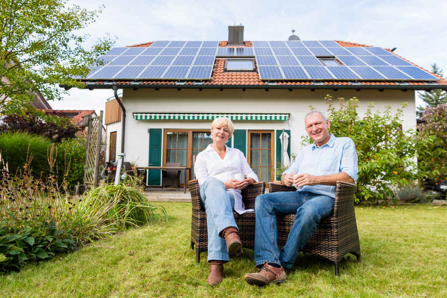 Old-Couple-sitting-in-front-of-their-solar-powered-home (tax credit)