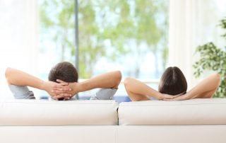 couple relaxing on a sofa at home and looking at window - Sound Reduction Package is a Standard on Our Windows