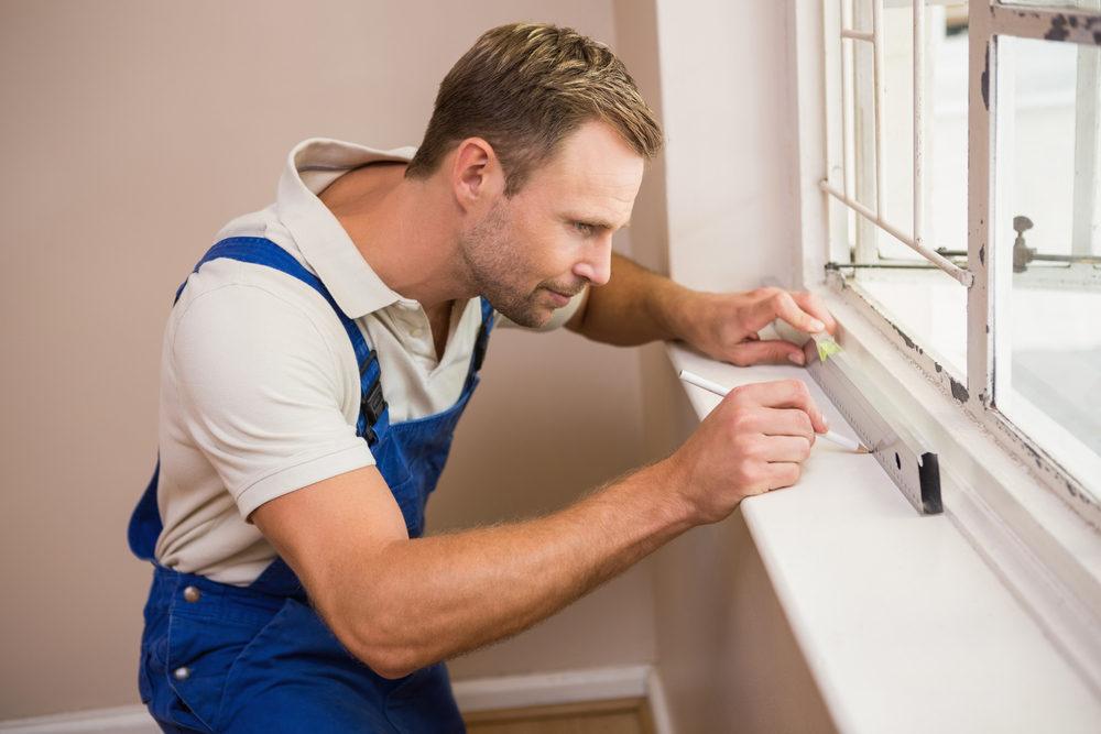 Man using spirit level to install new windows